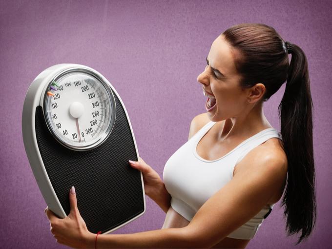 体重計に叫ぶ女性