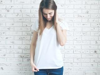 着ている白いTシャツを眺める女性