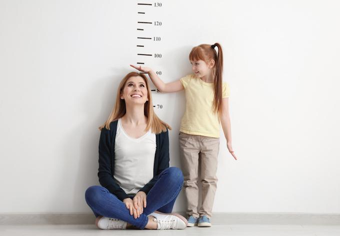目盛りの前で身長を図る女性と女の子の画像