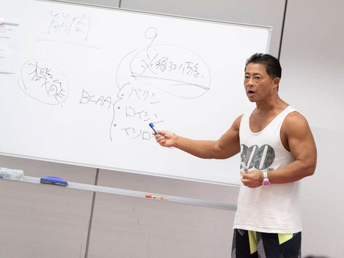 ホワイトボードの前で話すコンディショニングトレーナーの桑原弘樹先生