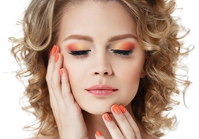 オレンジ色のアイメイクとネイルを施した女性の画像