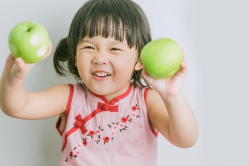 両手に青りんごをもった小さい女の子