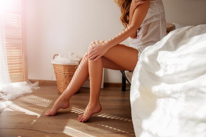 ベッドサイドで美脚を気にする女性