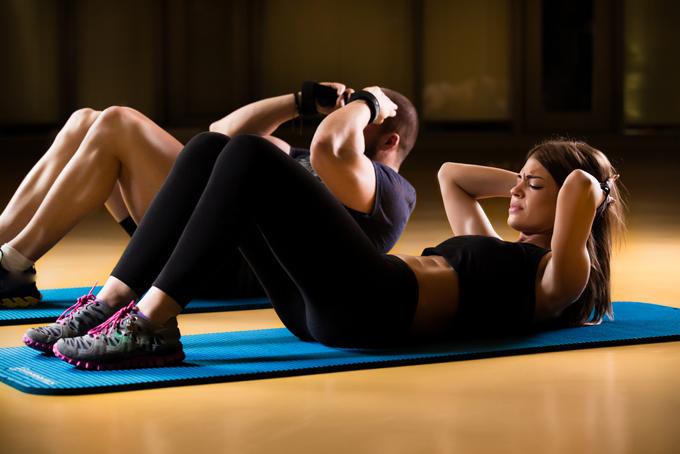 腹筋トレーニングをする男女の画像