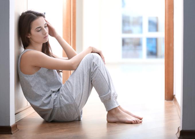 元気のない様子で床に座り込んだ女性の画像