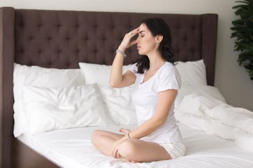 ベッドの上で瞑想をしている女性