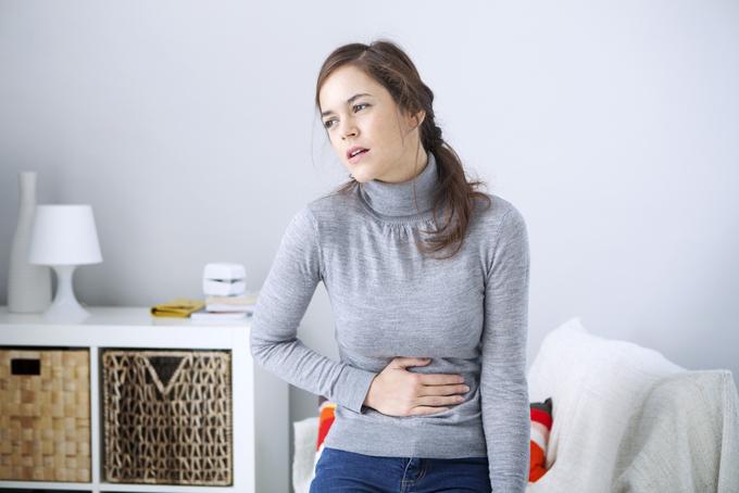 下腹部を押さえている女性の画像