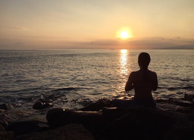 アンジェラさんが夕方の海辺で瞑想している