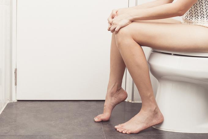 トイレの便座に座っている女性の足元