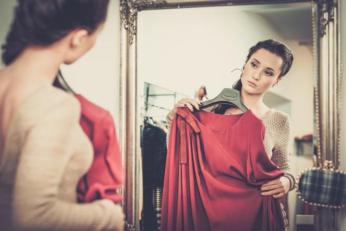 鏡を見ながら服を選んでいる女性の画像