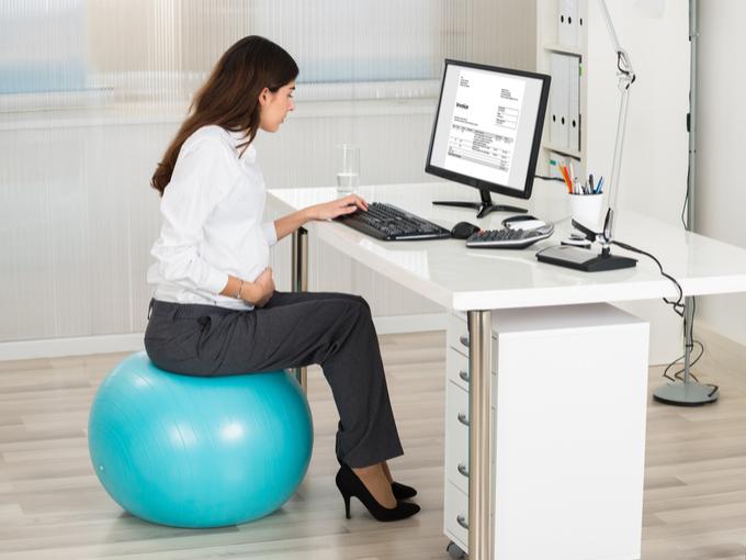 バランスボールに座ってデスクワークしている女性