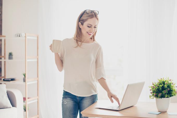立ながらパソコンを見る女性