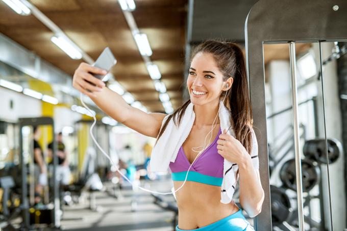トレーニングウェア姿で自撮りをする女性の画像