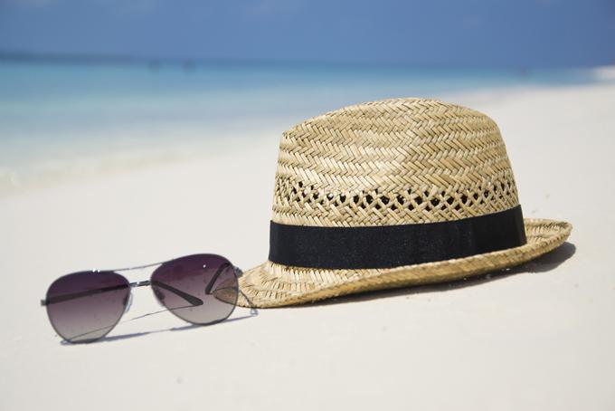浜辺に置かれた麦わら帽子とサングラスの画像