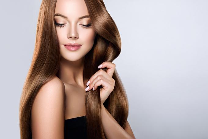 ロングヘアーの髪をなでている女性の画像