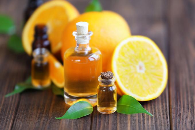 オレンジの果実と瓶に詰められたオイルの画像
