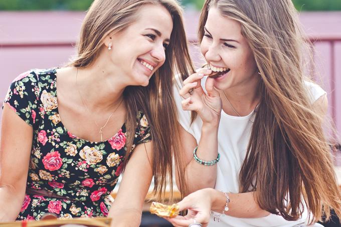 友だちとお菓子を食べる女性