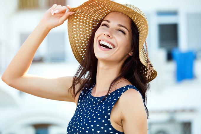 帽子を被った女性が笑っている画像