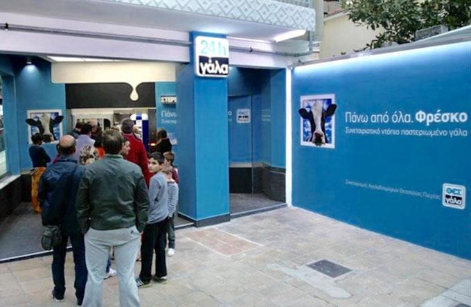 自動販売機でミルクを買い求めるギリシャの人たち