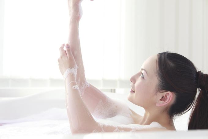 バスタブに浸かって泡で腕を洗っている女性