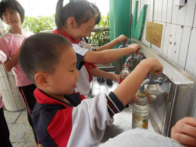 学校でお湯をくんでいる子ども達