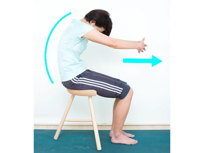 両手をつないで前に伸ばし、背中を丸めながらお腹を縮めます