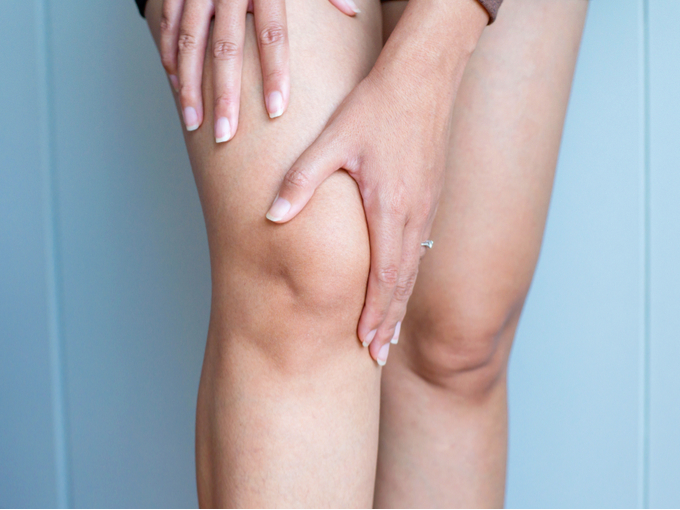 右ひざをおさえる女性