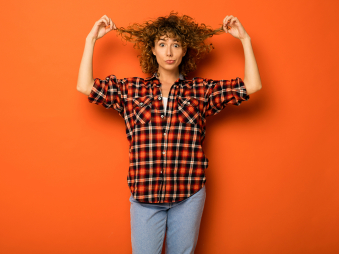 髪をつまんで見せる女性