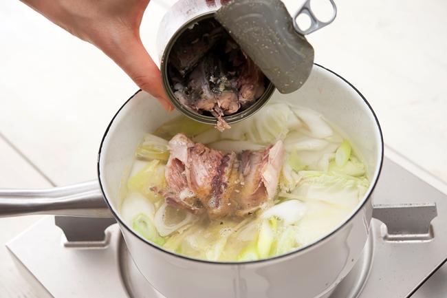 鍋にサバ缶を入れている写真