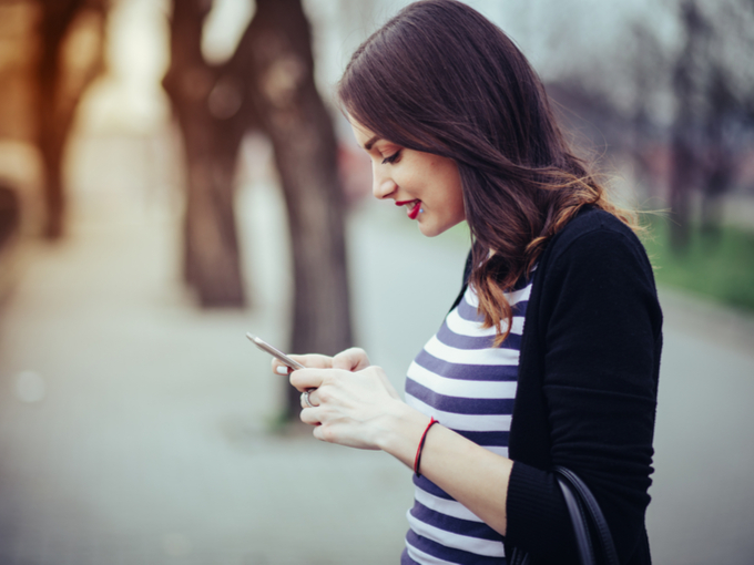 スマホ画面を見ている女性の画像