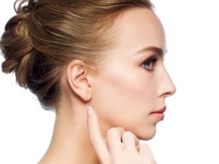 耳下を触ろうとしている女性の横顔