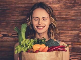 野菜の入った袋を抱えた笑顔の女性