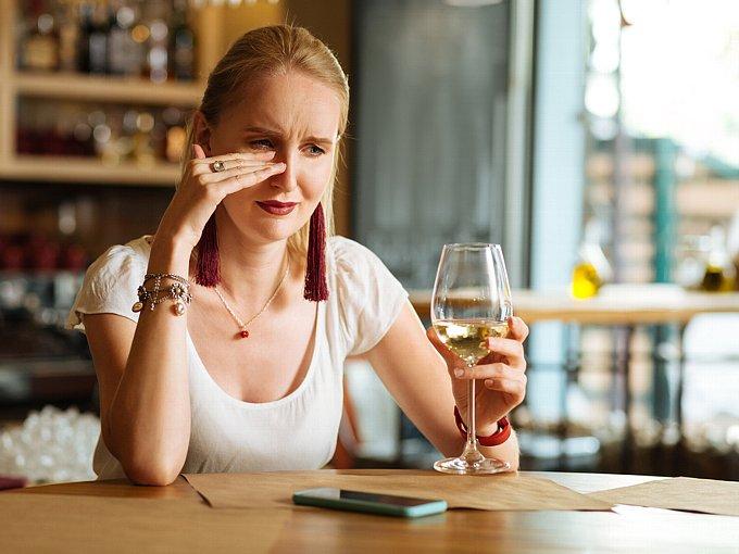 お酒を飲みながら泣く女性