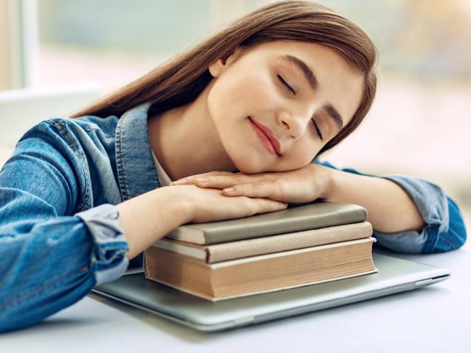 本を積み上げて寝ている女性の画像