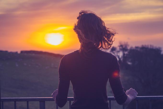 キレイな夕日を眺めている女性の後ろ姿