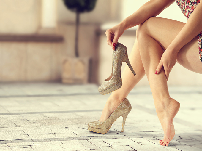 ヒール靴を脱いで脚をさすっている女性の脚画像