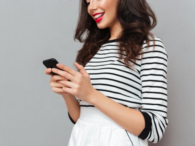 スマホを見て笑う女性の画像