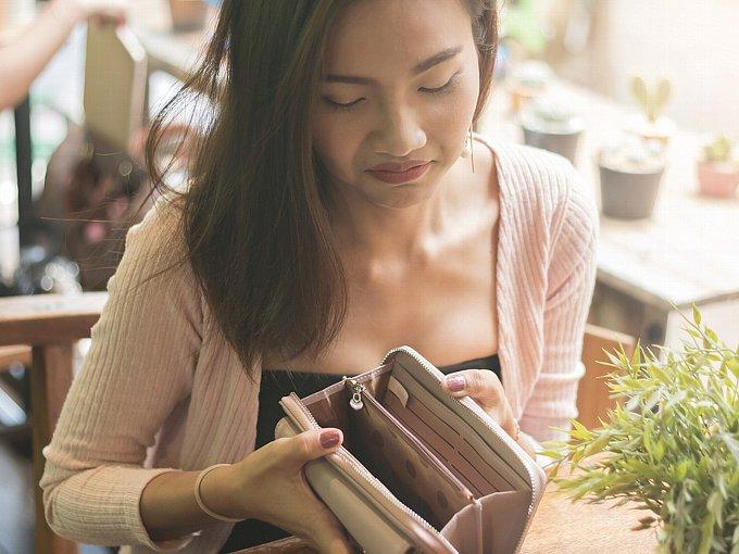 空っぽのお財布を見て、浮かない表情の女性