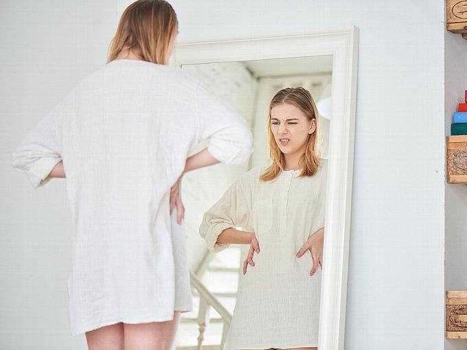 鏡の前で渋い顔をする女性