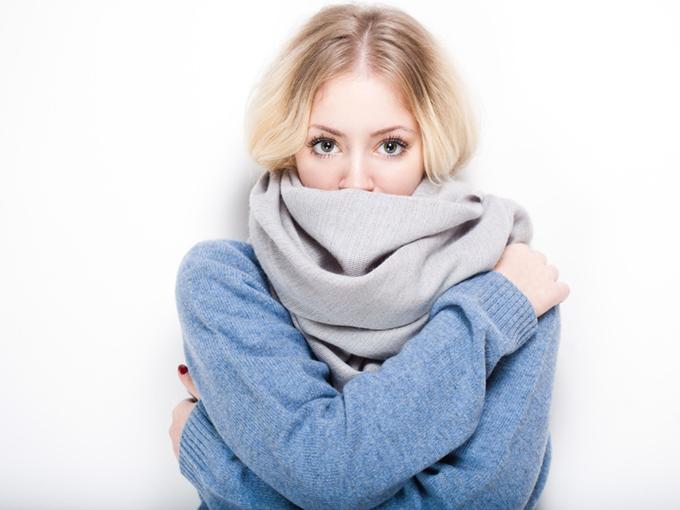 冬物の服やマフラーで着ぶくれしている女性