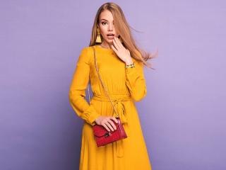 黄色い長そでのワンピースを着て、驚きの表情をうかべる女性