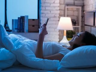 寝る前、ベッドでスマホをいじっている女性