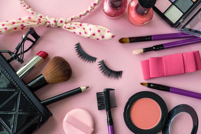 ピンクの背景に置かれたメイク道具の画像