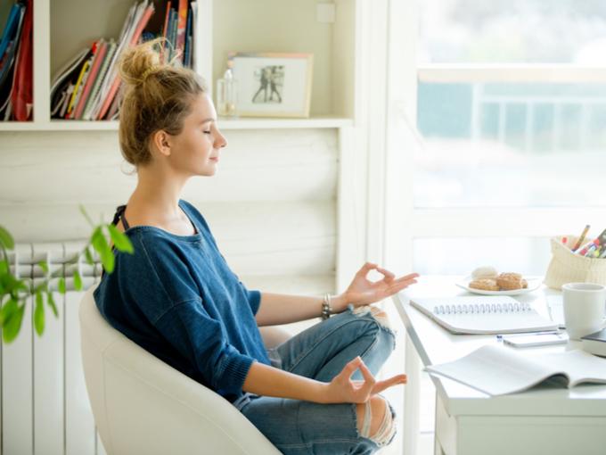 オフィスのデスクで坐禅を組んでいる女性の画像