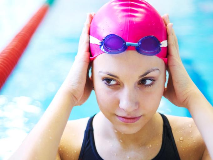 女性がプールの中で水泳帽を整えている画像