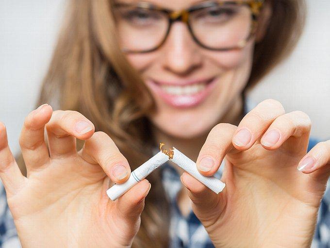 タバコを半分に割る女性