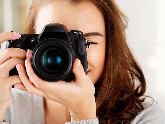 カメラのレンズをこちらに向ける女性