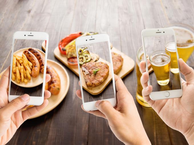 食事の写真をスマホで撮っている画像