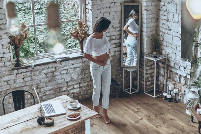 全身を鏡で映して体形を確認する女性