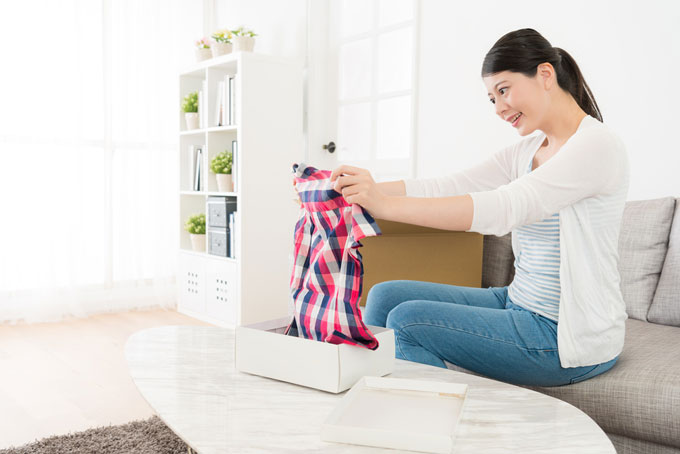 箱から洋服を取り出している女性の画像